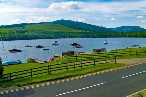Küstenstraße mit Blick auf den See mit Booten