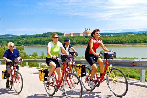 Radfahrer verlassen Melk und dessen Stiftskirche im Hintergrund