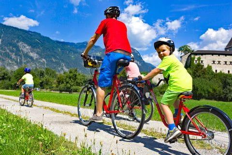 Junge radelt mit Vater auf dem Radweg