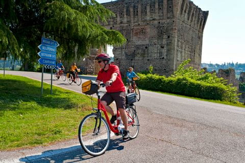 Cyclists passing the old ruin of Borghetto
