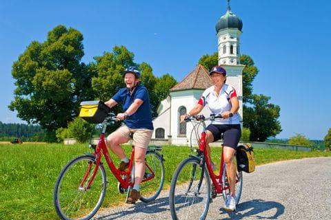 Zwei Radfahrer die an einer kleinen Kirche vorbei fahren