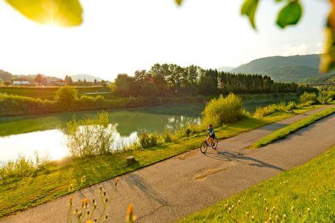 Cyclists on cycle path along the river Drau