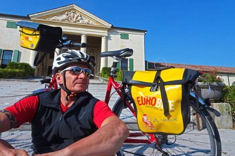 Radfahrer macht eine Pause vor einem Schloss