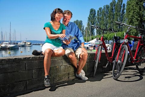 Cyclists having a break at promenade at Lake Constance