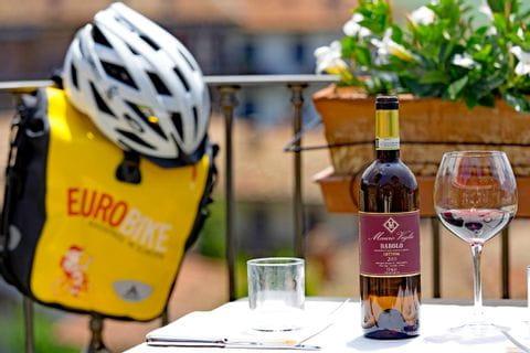 Eurobike Radtasche und Radhelm neben Tisch mit Wein