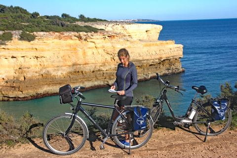 Cyclist and bikes in front of the sea and rocks
