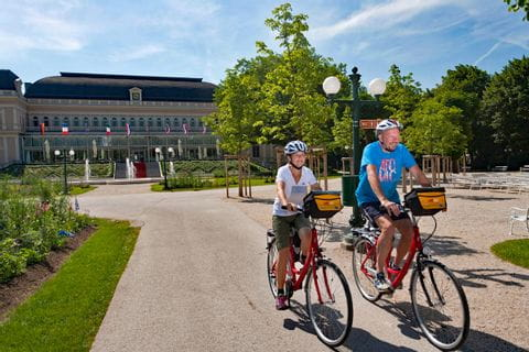 "Two cyclists in front of the ""Kurhaus"" in Bad Ischl"