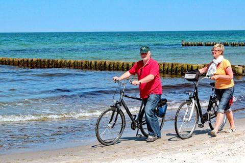 Radfahrer die ihr Rad am Strand entlang schieben in Nordfriesland