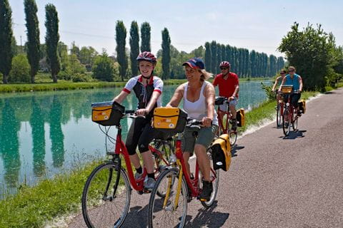 Cyclists riding along the river Adige