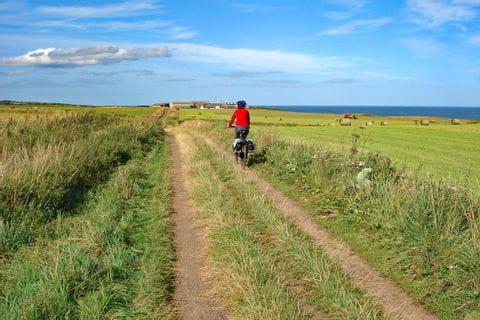 Feldradweg mit Blick auf Heuballen und dem Meer