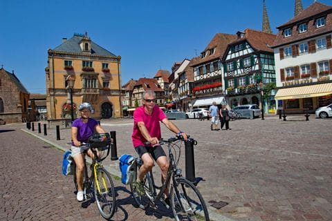 Radfahrer radeln durch ein typische Kleinstadt im Elsass