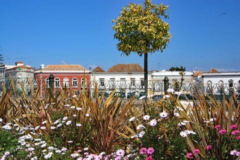 Von Blumen gesäumte Promenade vor einer typischen Häuserfront an der Algarve