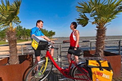 Zwei Radler und ein Eurobike-Fahrrad vor dem Neusiedlersee