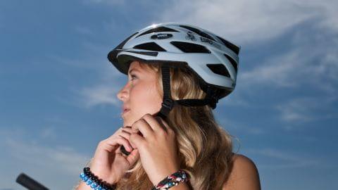 Mädchen zieht ihren Fahrradhelm fest.