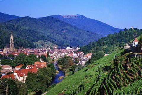 Blick über die zwischen Hügeln im Elsass eingebettete Stadt Thann