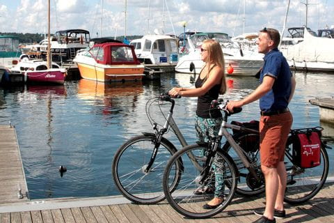 Cyclists at the jetty with view of boats