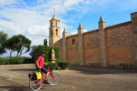 Cyclist in front of the church of Son Negre