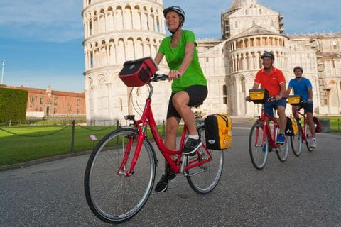 cyclists in front of the tower of Pisa