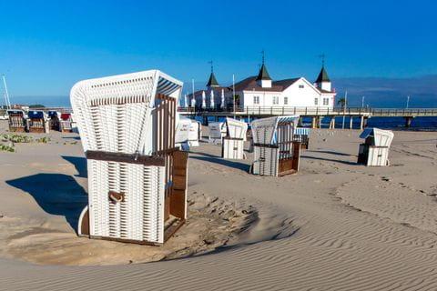 Strandkorb mit Strandhaus im Hintergrund