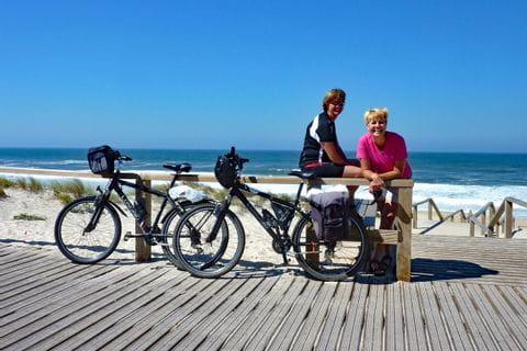 Zwei Frauen mit Rädern am Strand