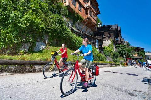 Radfahrerinnen vor antikem Holzhaus in Hallstatt