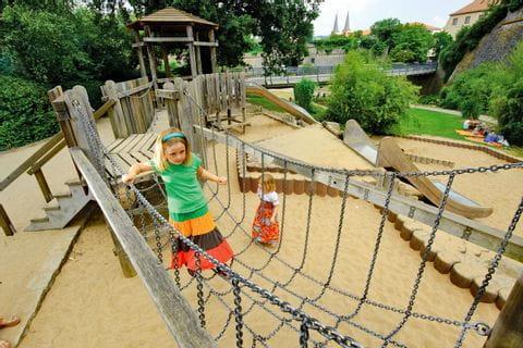 Mädchen spielt am Spielplatz mit Festungsgraben in Würzburg