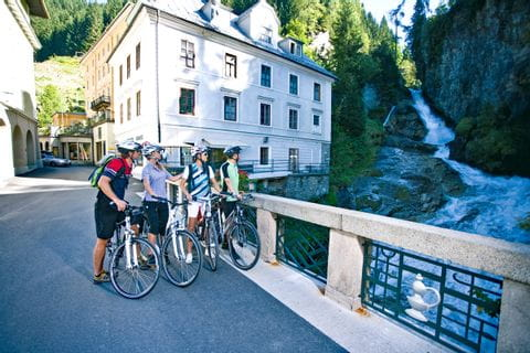 Cyclists on a bridge watching a small waterfall