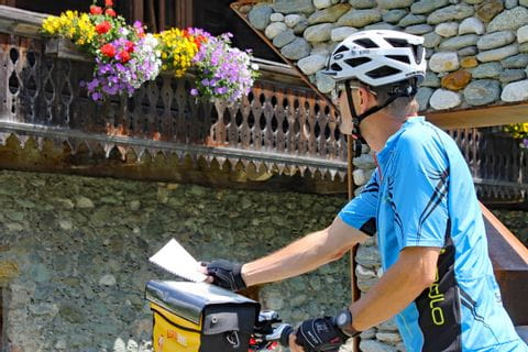 Cyclist in front of stone house with flowers