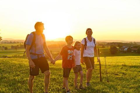 Familie wandert beim Sonnenuntergang