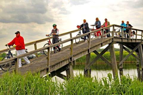 Radfahrer überqueren Holzbrücke