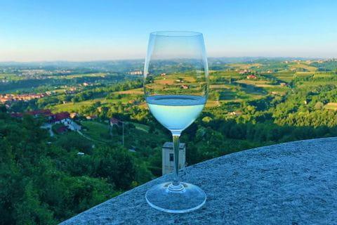 Weinglas vor einer wunderschönen Landschaft im schönen Piemont entlang der Turin nach Sanremo Tour