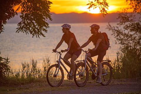 Radfahrer am Bodensee bei Sonnenuntergang