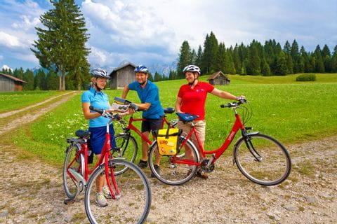 Drei Radfahrer unterhalten sich an einer Radkreuzung im Werdenfelser Land