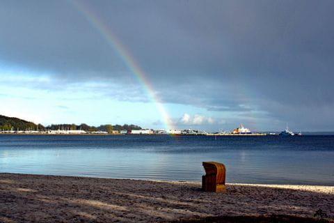 Strandkorb mit Regenbogen im Hintergrund