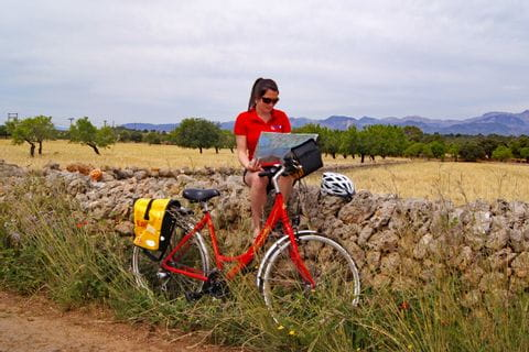 Cyclist is sitting on stone wall