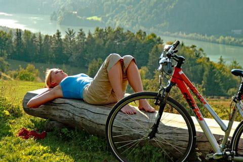 Cyclist enjoy the sun lying on a tree