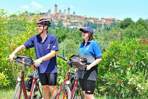 Two cyclists in front of the scenery of San Gimignano