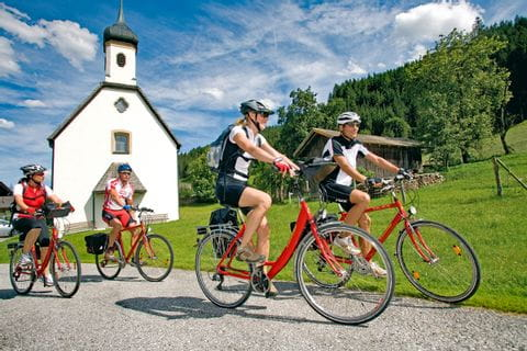 Cyclists passing a church