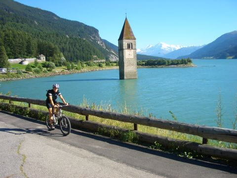 Cyclist in front of the sunken church in Graun