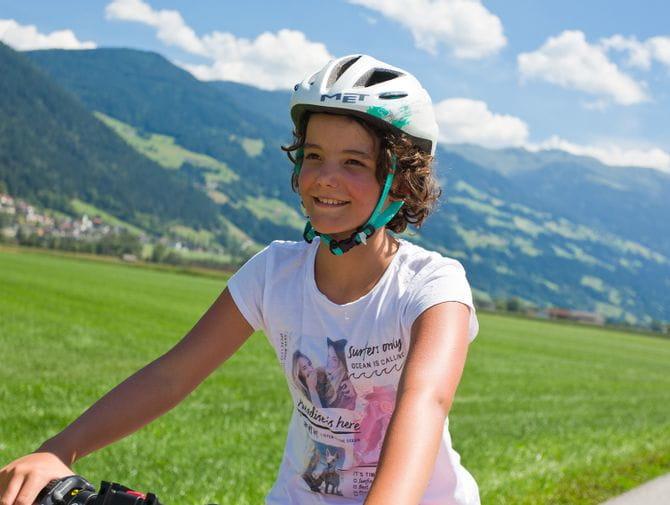 Mädchen mit Locken und Helm beim Fahrradfahren in grüner Hügellandschaft.