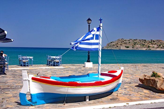 Boot mit griechischer Flagge am Meer
